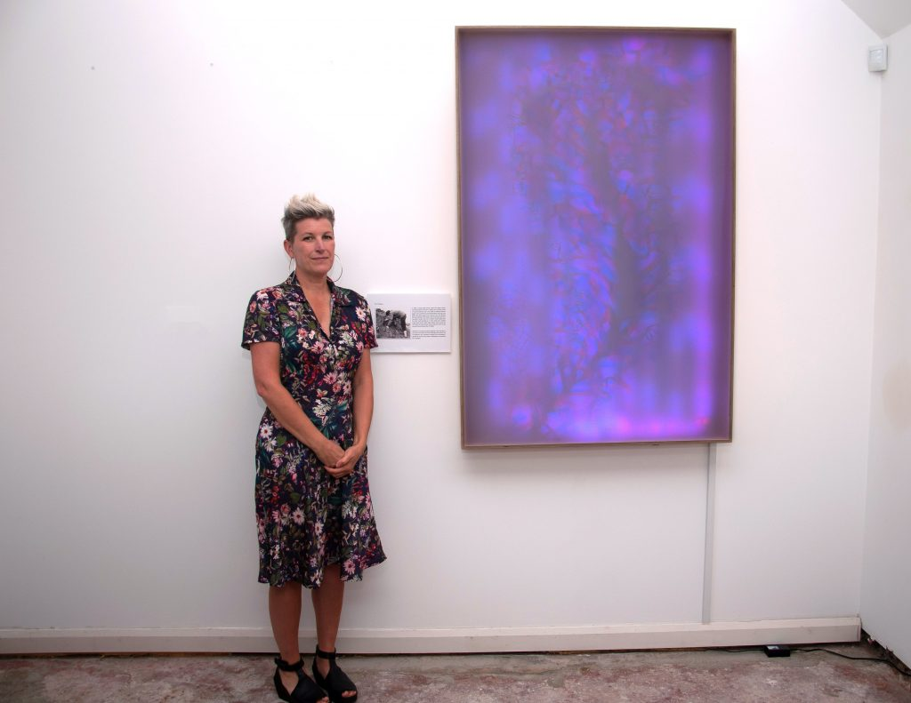 A picture of Jayne Childs next to a wall mounted lightbox Charnia 1